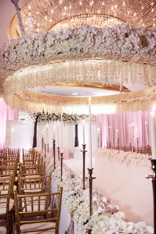 opulent-wedding-ceremony-tall-taper-candles-gold-chairs-white-flowers-orchid-chandelier-overhead