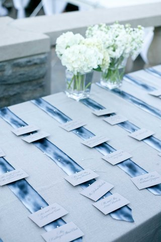 wedding-escort-cards-pinned-to-blue-silk-ties-on-table-with-grey-linen-and-white-flowers