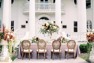 A Charming Fete Romantic Reception Table purple mauve linen cane chairs