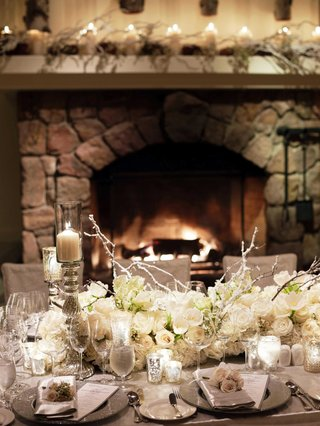 winter-wedding-ideas-for-reception-at-indoor-venue-with-fireplace-and-branch-centerpieces