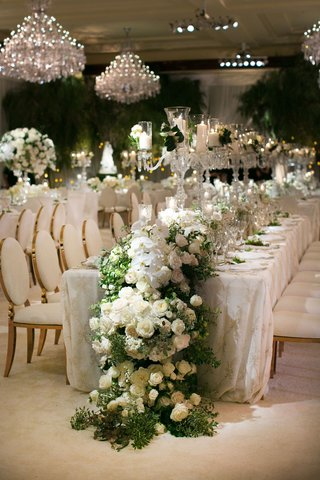 wedding-reception-long-table-with-gold-chairs-overflowing-flower-runner-white-orchid-rose-greenery