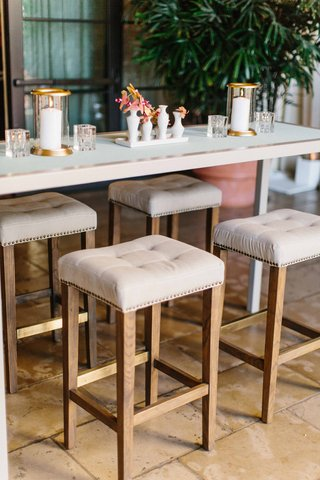 white-cocktail-table-with-tufted-nail-head-bar-stools-wood-legs-gold-candle-votives-pink-orchids