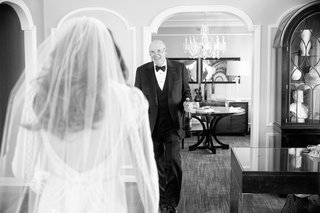 black-and-white-photo-of-father-of-the-brides-reaction-to-daughters-wedding-dress-holding-champagne