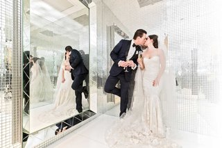 bride-and-groom-in-room-with-mirror-walls-veil-strapless-wedding-dress-champagne-kiss