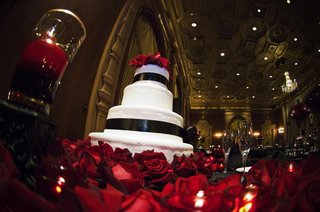 white-wedding-cake-with-black-satin-ribbon-surrounded-by-red-roses