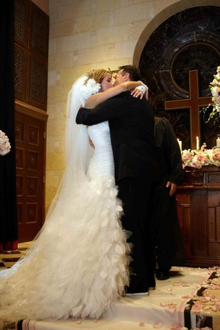 bride-and-groom-kissing-in-front-of-cross