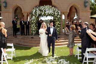 bride-and-groom-walk-up-grass-aisle-at-the-grand-del-mar