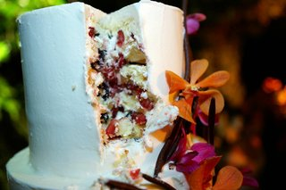 white-wedding-cake-with-berries-and-orchids