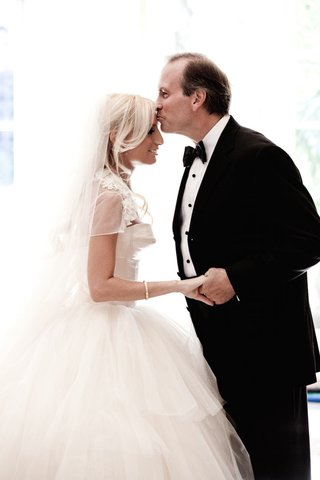 dad-in-tux-kisses-forehead-of-bride-in-ball-gown