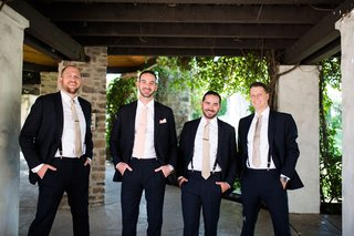 groom-in-pink-tie-groomsmen-in-suits-suspenders-champagne-tie-tie-clips-hands-in-pockets