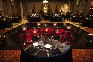 wedding-reception-sweetheart-table-with-black-linens-red-roses-and-black-candleholders