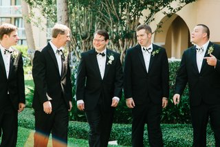 groomsmen-in-black-suite-and-black-and-white-bow-ties-with-greenery-boutonnieres