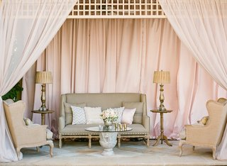 wedding-reception-lounge-area-draped-in-pink-fabric-with-elegant-furniture