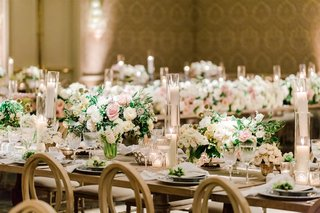 wedding reception ballroom candles and low arrangements of greenery and white pink flowers