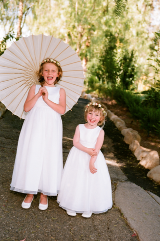 two-flower-girls-in-white-dresses-with-one-holding-parasol