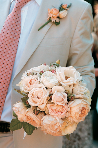 groom-holds-bouquet-with-peach-and-white-peonies