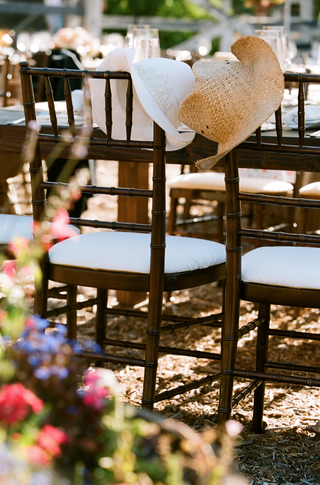 cowboy-hats-on-back-of-bride-and-groom-chairs