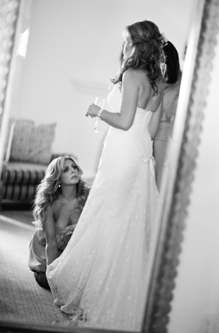 black-and-white-photo-of-bridesmaid-helping-bride-with-her-dress