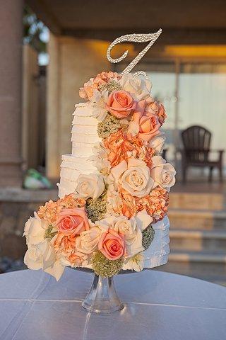 white-three-layer-wedding-cake-with-fresh-orange-and-white-rose-flowers-rhinestone-monogram-topper