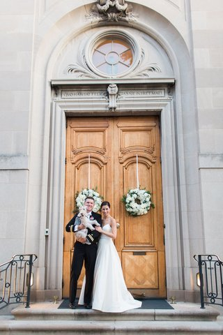 bride-and-groom-in-front-of-meridian-house-wedding-venue-with-dog-puppy-fox-terrier-wreaths-tall