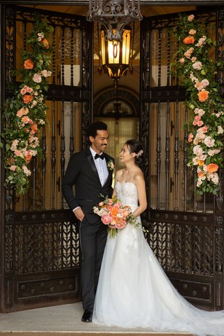 wedding-inspiration-styled-shoot-bride-in-mira-zwillinger-groom-in-tuxedo-gate-with-peachy-floral