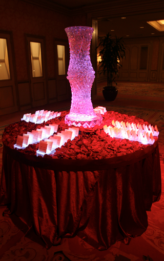 wedding-reception-place-card-table-covered-with-red-rose-petals-and-topped-with-a-vase-ice-sculpture