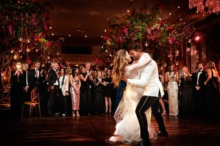 bride-in-vera-wang-wedding-dress-groom-in-white-jacket-first-dance-beautiful-photo-dip-guests-watch