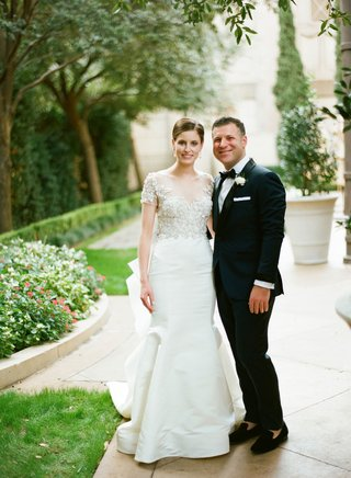 bride-in-marchesa-wedding-dress-illusion-neckline-short-sleeve-fit-and-flare-groom-in-tuxedo-bow-tie