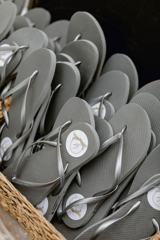 beach-wedding-favors-at-reception-grey-flip-flops-with-white-circle-sticker-tags-in-basket