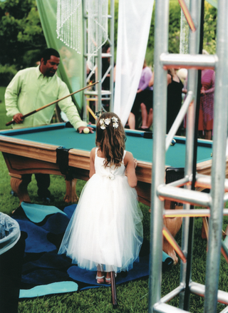 flower-girl-watching-guest-play-pool-at-custom-blue-suede-pool-tables