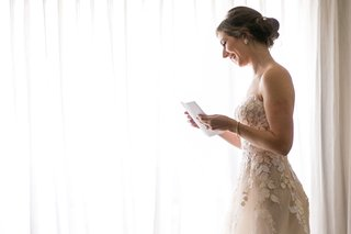 wedding-bridal-suite-getting-ready-strapless-wedding-dress-reading-note-from-groom-husband