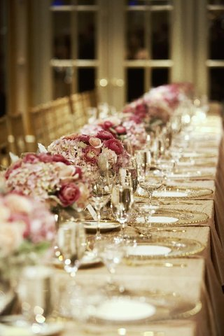 gold-rimmed-charger-plates-and-pink-floral-arrangements