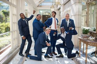 a-groom-and-his-groomsmen-playfully-pose-in-blue-suits-with-varying-ties-before-ceremony