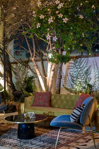 wedding-reception-outdoor-lounge-area-round-cocktail-table-tufted-green-sofa-mid-century-blue-chair