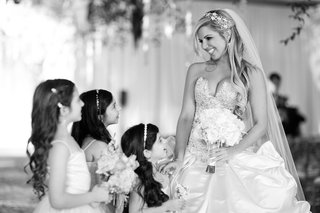 black-and-white-photo-of-bride-smiling-at-flower-girls