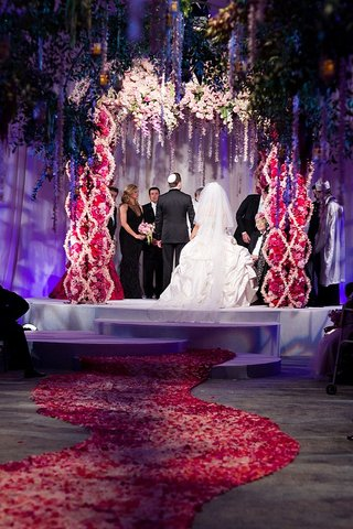 bride-and-groom-under-flower-chuppah-at-indoor-garden-ceremony