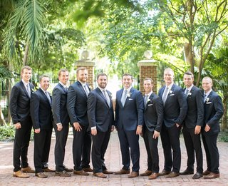 groom-in-light-blue-tie-and-groomsmen-in-dark-suits-with-grey-ties-and-brown-dress-shoes