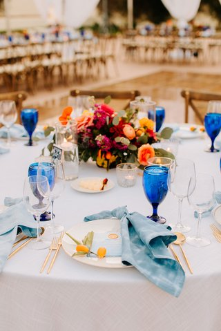 wedding reception place setting with blue napkin kumquat fruit and goblet colorful flowers talavera tile