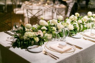 white-rectangular-table-with-garland-runner-of-white-flowers-and-greenery