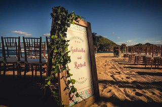 a-couples-colorful-ceremony-sign-greenery-for-their-destination-wedding-in-cabo-san-lucas-mexico