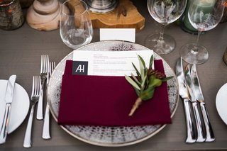 wedding-reception-grey-wash-wood-table-wood-plank-riser-burgundy-napkin-sprig-of-greenery-silver