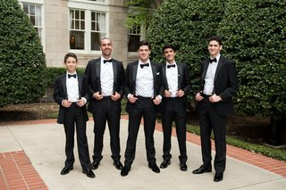groom-groomsmen-young-groomsmen-in-classic-black-tuxedos-tug-on-suspenders