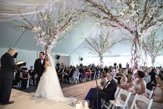 bride-and-groom-on-stage-in-front-of-officiant-with-tree-decorations