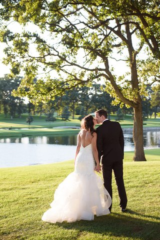 bride-in-monique-lhuillier-mermaid-wedding-dress-and-groom-in-gibeon-tolbert-kiss-golf-course