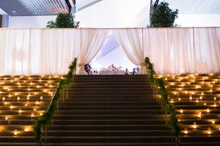 stairs-up-to-couples-wedding-reception-small-candles-greenery-railing-white-fabrics