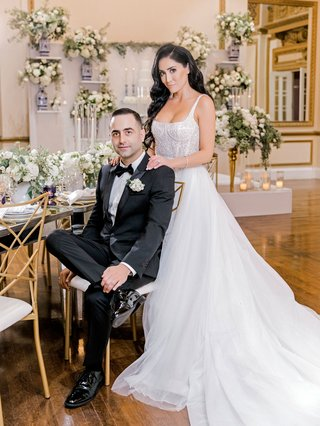 wedding-portrait-of-bride-and-groom-in-reception-ballroom-blue-and-white-decor-greenery-gold-details