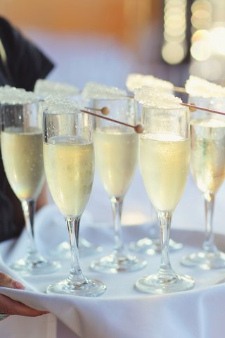 wedding-reception-with-tray-of-champagne-flutes-and-rock-candy-wands