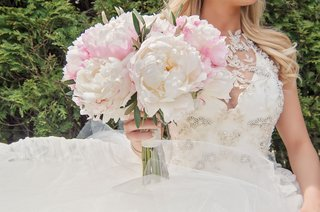 bride-in-vera-wang-dress-holding-pink-peony-bouquet-with-rosary-of-grandmother-wrapped-around-stems