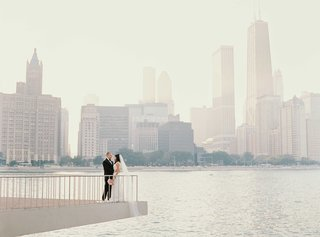 bride-and-groom-on-ledge-over-river-in-chicago-with-skyline-in-background