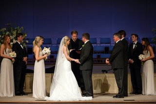 bride-in-a-strapless-fit-and-flare-wedding-dress-and-veil-with-groom-in-a-black-tuxedo-at-altar